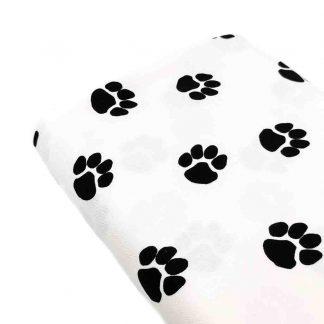 Tela de loneta de algodón estampada con huellas de perro negras sobre fondo color blanco. Dog Paw Designed for you by POPPY Europe
