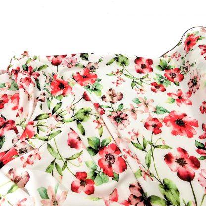 Tela seda estampada con flores de colores sobre fondo color coral.