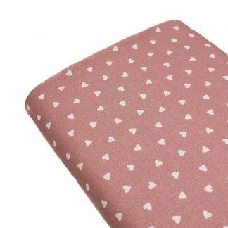 Tela de popelín de algodón orgánico estampado con corazones sobre fondo rosa palo